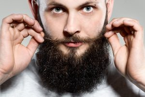 man with beard adjusting his mustaches
